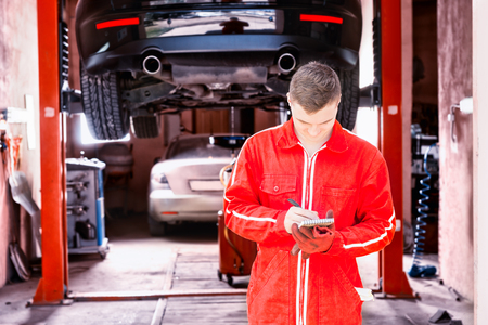 Young male motor mechanic standing making notes in front of a black sedan elevated on a hoist in a bay in a garage or workshop