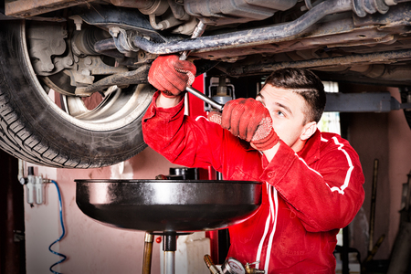 Male auto mechanic in uniform working underneath a lifted car and changing motor oil in automobile engine at maintenance repair service station in a car workshop
