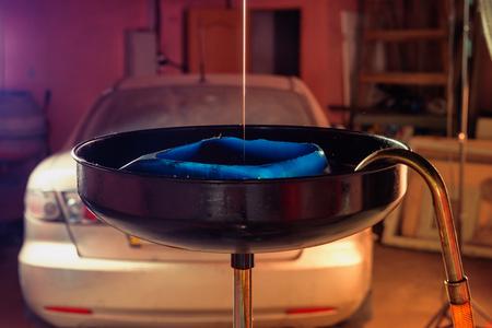 El cierre del chorro de aceite fluye hacia el equipo para cambiar el aceite del motor en un motor de automóvil en un taller de automóviles o en un garaje