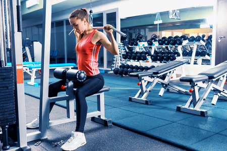 Sportive woman in sportswear doing exercise with a heavy weight using training apparatus in a gym