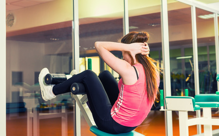 Sporty woman doing sit-up using training apparatus in a gym Stock Photo