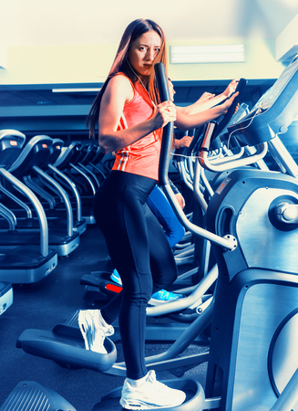 Young woman diligently exercising on the crosstrainer machine in fitness center Stock Photo