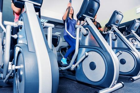 Onderaanzicht op groep mensen die op de crosstrainer machines in het fitnesscentrum hard werken Stockfoto