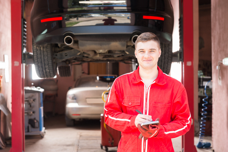 Smiling male motor mechanic standing making notes in front of a black sedan elevated on a hoist in a bay in a garage or workshop