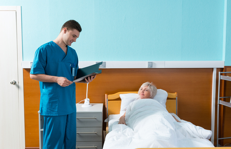 recuperation: Male doctor looks at the analysis scores of his female patient, who is lying in the hospital bed in the hospital ward. Healthcare concept