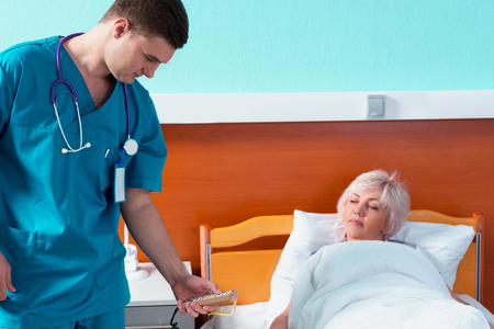 Young doctor in uniform with phonendoscope on his neck regulates a hospital bed of his female patient using a special console in the hospital ward. Healthcare concept