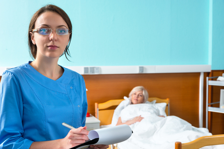 recuperation: Young female nurse or doctor in uniform wearing a mask and glasses making some notes in report at clipboard while visiting her ill patient in the ward. Healthcare concept Stock Photo