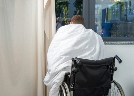 Ill patient sitting by the window on wheelchair covered with quilt in hospital ward. Healthcare concept Stock Photo