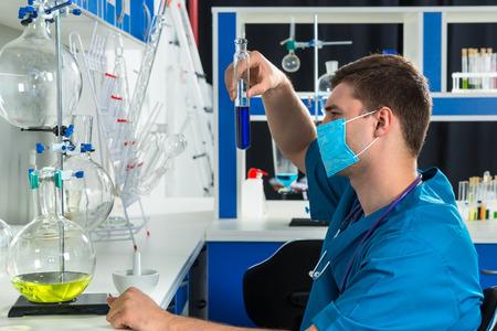 Un jeune scientifique en uniforme portant un masque tient un grand tube à essai avec un liquide bleu, faisant des recherches en laboratoire. Concept santé et biotechnologie