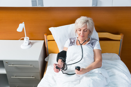 recuperation: Patient is measuring the arterial pressure using a medical equipment, while lying in the hospital bed in the hospital ward. Healthcare concept Stock Photo