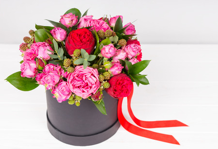 Lovely bouquet of pink and red roses and red ribbon in a circular black box on white wooden table. Valentines and anniversary concept