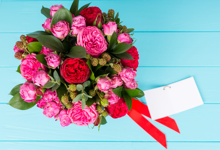 View from above on fashionable bouquet of pink and red roses with a blank gift tag with copy space and red ribbon in a circular black box. Valentines and anniversary concept