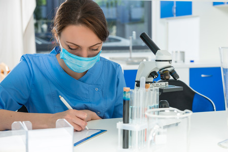 Young female scientist in uniform writing down notes of her research in a laboratory. Healthcare and biotechnology concept