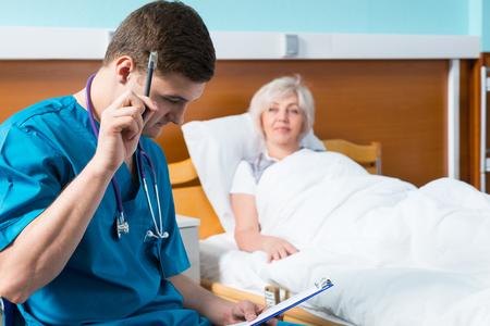 recuperation: Handsome thoughtful doctor in uniform with phonendoscope on his neck writing down complaints of patient, who is lying in the hospital bed in the hospital ward. Healthcare concept Stock Photo