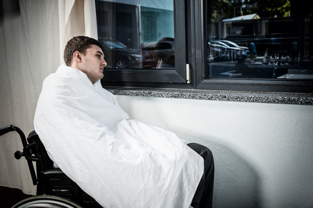 Sad male ill patient sitting by the window on wheelchair covered with quilt in hospital ward. Healthcare concept