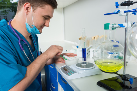balanza de laboratorio: Young male scientist in uniform wearing a mask weighs powder on special scales for some research in a laboratory. Healthcare and biotechnology concept