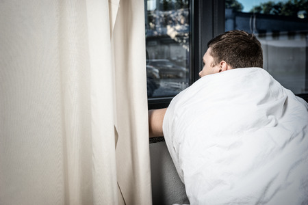 Sad male patient sitting by the window on wheelchair covered with quilt in hospital ward. Healthcare concept