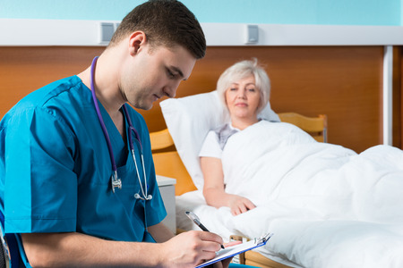 Handsome young male doctor in uniform with phonendoscope on his neck writing down complaints of patient, who is lying in the hospital bed in the hospital ward. Healthcare concept Stockfoto