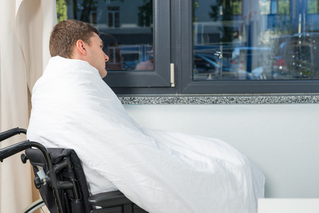 Male ill patient sitting by the window on wheelchair covered with quilt in hospital ward. Healthcare concept