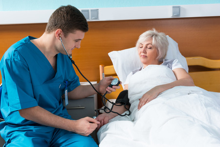 Young male doctor in uniform with phonendoscope is measuring the arterial pressure of his female patient using a medical equipment, who is lying in the bed in the hospital ward. Healthcare concept 免版税图像
