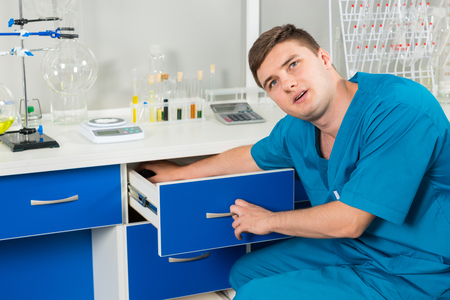 Handsome young lab assistant is looking for something in a cases in a laboratory. Healthcare and biotechnology concept