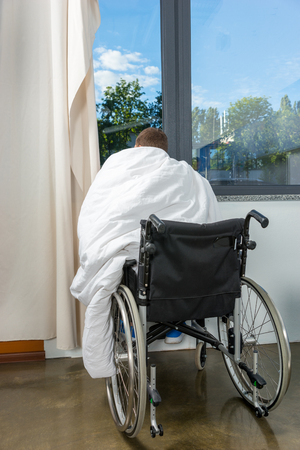 Male young patient sitting by the window on wheelchair covered with quilt in hospital ward. Healthcare concept Stock Photo