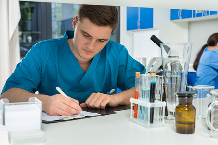 Young male scientist in uniform writing down notes of his research in a laboratory. Healthcare and biotechnology concept Stock Photo