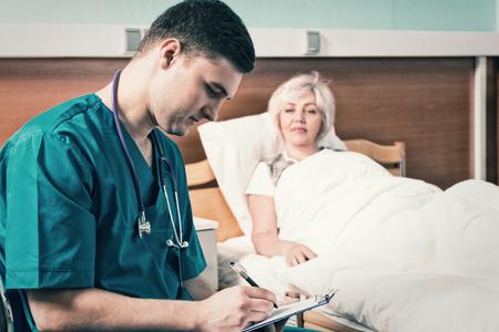 Knappe jonge arts in eenvormig met phonendoscope op zijn hals die klachten van patiënt neerschrijven, die in het het ziekenhuisbed in de het ziekenhuisafdeling ligt. Gezondheidszorg concept