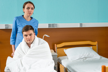 Attractive young nurse pulling wheelchair with ill patient covered with quilt in hospital ward. Healthcare concept