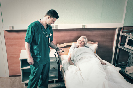 recuperation: Doctor in uniform with phonendoscope on his neck regulates a hospital bed of his female patient using a special console in the hospital ward. Healthcare concept