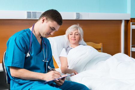 Handsome male doctor in uniform with phonendoscope on his neck writing down complaints of patient, who is lying in the hospital bed in the hospital ward. Healthcare concept
