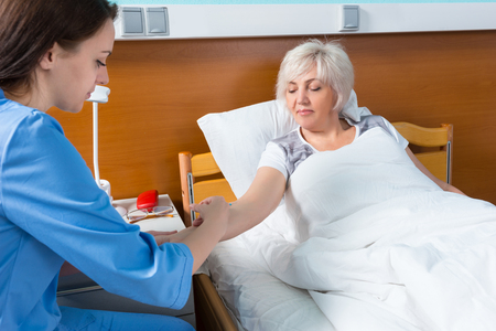 Female doctor in uniform is doing an injection to her patient, who is lying in the hospital bed in the hospital ward. Healthcare concept Stock Photo