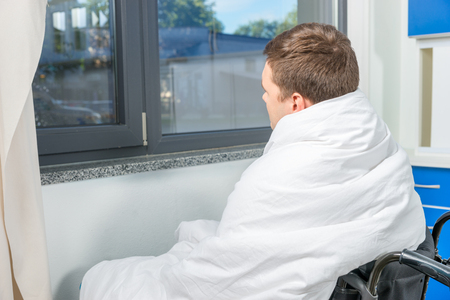 Sad ill patient sitting by the window on wheelchair covered with quilt in hospital ward. Healthcare concept