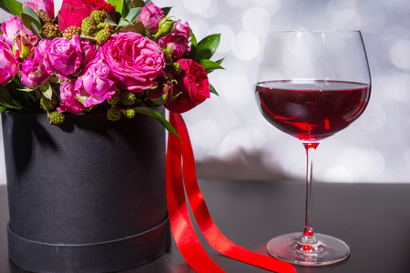 Lovely bouquet of pink and red roses and red ribbon in a circular black box near a glass with wine. Valentines and anniversary concept