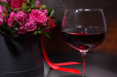 Centrepiece: Close up of glass with wine standing by bouquet of pink roses