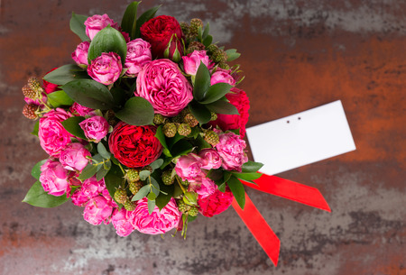 Beautiful bouquet of pink roses with gift tag and red ribbon in a concept of love, romance, anniversary, Valentines day or wedding