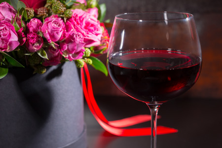 Beautiful bouquet of pink and red roses and red ribbon in a circular black box near a glass with wine. Valentines and anniversary concept