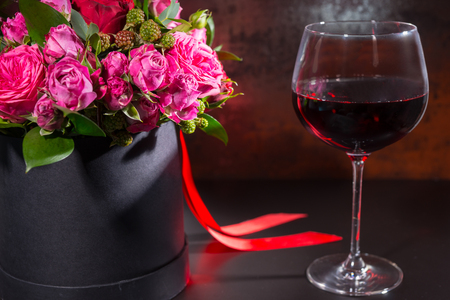 Bouquet of pink and red roses and red ribbon in a circular black box near a glass with wine. Valentines and anniversary concept Stock Photo