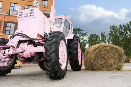Fancy pink tractor next to a haystack, old brick building in the background, countryside concept