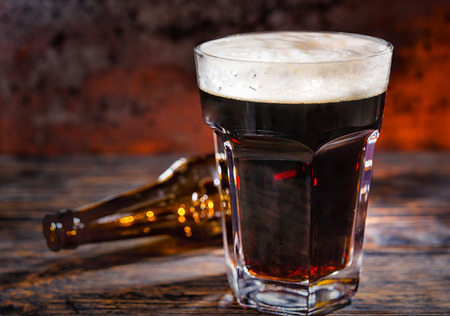 Glass of freshly poured dark beer near empty bottle on dark wooden desk. Food and beverages concept Stock Photo