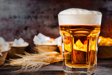 Big glass with freshly poured beer and head of foam near plates with snacks on dark wooden desk. Food and beverages concept