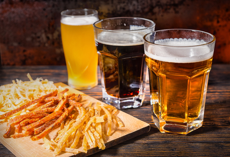 Three glasses with freshly poured light, unfiltered and dark beer stand near wooden cutting board with dried fish and squid on dark desk. Food and beverages concept