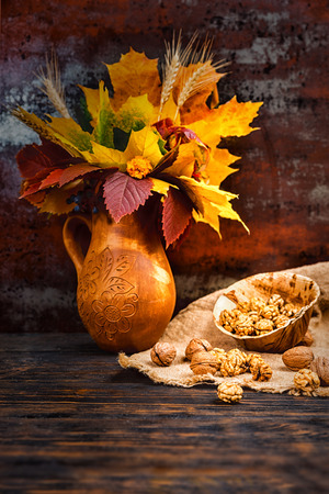 Wooden plate with walnuts on linen cloth near clay jug with autumn leaves. Mockup for seasonal offers and holiday post card
