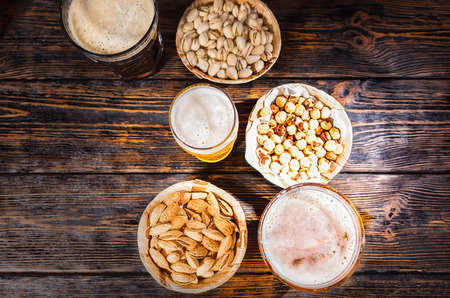 Top view of three glasses with light, unfiltered and dark beer near plates with different nuts on dark wooden desk. Food and beverages concept