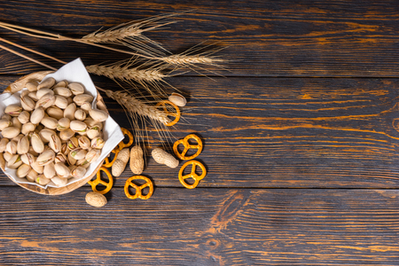 Top view of wooden plate with pistachios near wheat, scattered small pretzels and peanuts on old dark desk. Food and beverages concept