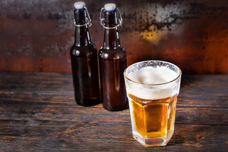 Two beer bottles near glass with a light beer and a head of foam on old dark desk. Drink and beverages concept