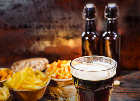Plates with snacks near two bottles and a glass of dark beer, wheat, scattered nuts and pretzels on dark wooden desk. Food and beverages concept