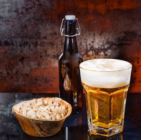 Glass with freshly poured light beer, beer bottle near wooden plate with pistachios on a black mirror surface. Food and beverages concept Stock Photo