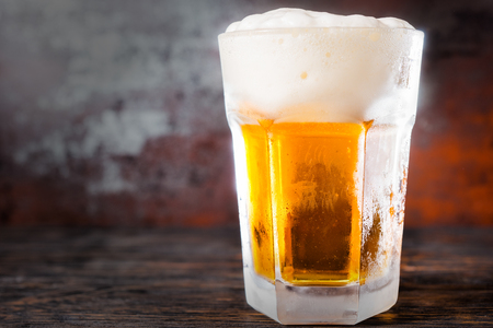 Big glass with a light beer and a large head of foam on old dark desk. Drink and beverages concept