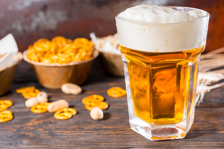 Focus on light beer and a head of foam near plate with small pretzel on dark wooden desk. Food and beverages concept Stock Photo